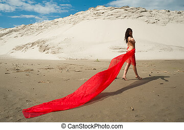 Attractive naked girl with red scarf on sand