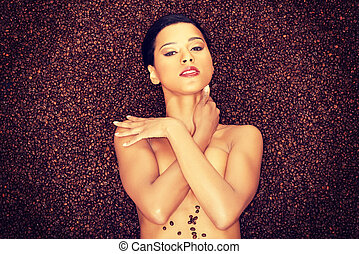 Attractive naked woman lying in coffee grains.