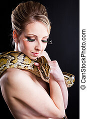 attractive nude blond woman with python on black