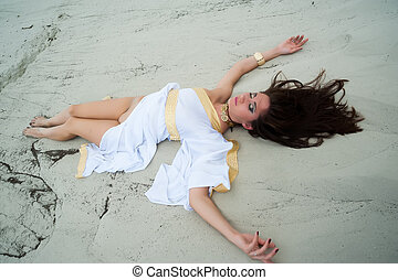 Attractive nude woman lay on sand