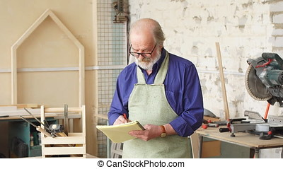 Attractive old carpenter working on designs in his workshop....