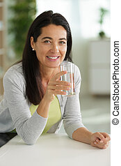 attractive older woman holding a glass of water