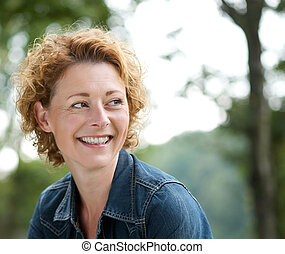 Attractive older woman smiling and looking away