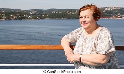 Attractive older woman stands on ship deck