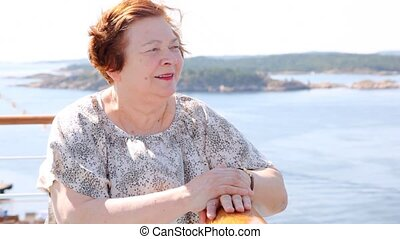 Attractive older woman stands on ship deck in sunny weather