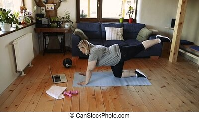Attractive overweight woman at home exercising on a mat. -...