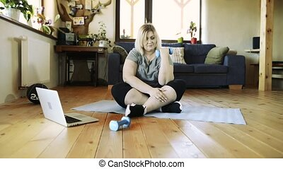 Attractive overweight woman at home working out with barbells.