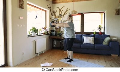 Attractive overweight woman at home working out with medicine ball.