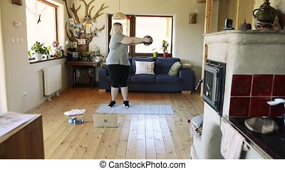 Attractive overweight woman at home working out with ...