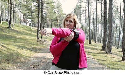 Attractive overweight woman in park doing stretching before...