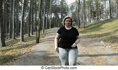 Attractive overweight woman running with a smartwatch. -...