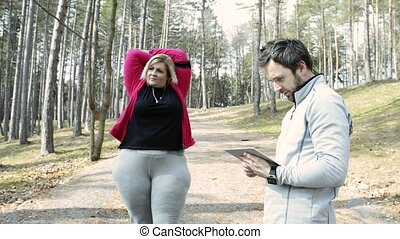 Attractive overweight woman with a trainer in park, stretching before running.