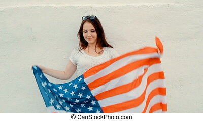 Attractive patriotic young woman holds American Flag before her body while dancing in front of wall celebrating forth of july