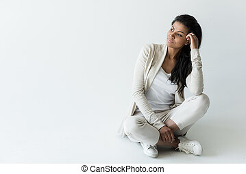 attractive pensive african american woman sitting on white with copy space