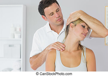 Attractive physiotherapist examining patients neck in bright...