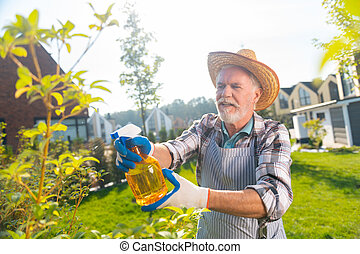 Attractive pleasant retired man taking care of the garden