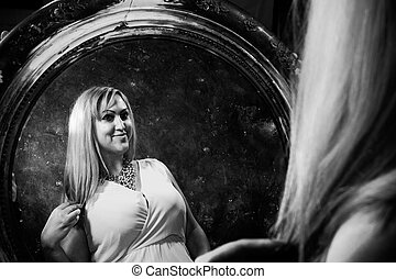 Attractive plump woman looking at her reflection at retro style mirror