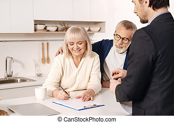 Attractive positive aged couple signing documents at home