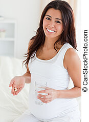 Attractive pregnant woman holding a glass of water and pills while sitting on a bed at home