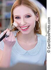 Attractive pretty blonde woman applying beautiful makeup