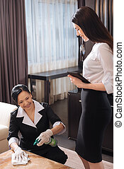 Attractive professional manager looking at the chamber maid...