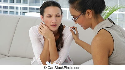 Attractive psychoanalyst talking with young woman at therapy...