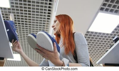 Attractive rd haired woman chooses a sneakers in shoes store - shopping concept