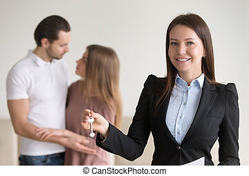 Attractive real estate agent holding keys to apartment, property