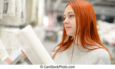Attractive red girl shopping for bedding in large mall