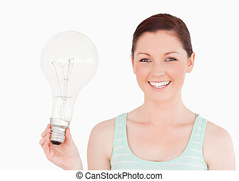 Attractive red-haired female holding a bulb while standing