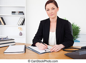 Attractive red-haired female in suit writing on a notepad