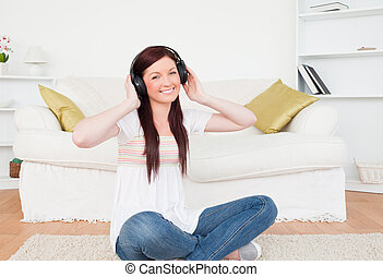 Attractive red-haired female listening to music with headphones while sitting on a carpet in the living room