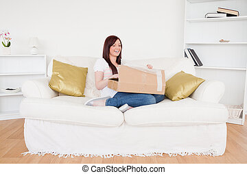 Attractive red-haired female opening a cardboard box