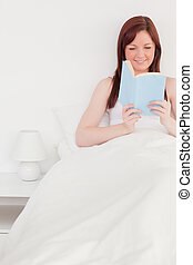 Attractive red-haired female reading a book while sitting on her bed