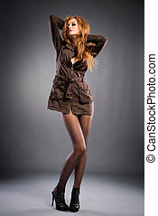 Attractive red-haired girl wearing casual dress and high heels shoes . Studio shot