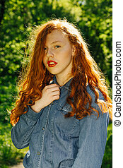 Attractive red haired model in blue jeans shirt in rays of sun at the park