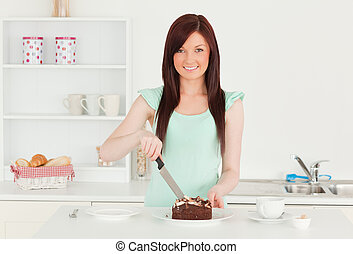 Attractive red-haired woman cutting some cake in the kitchen