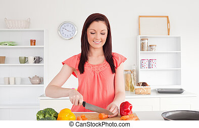 Attractive red-haired woman cutting some vegetables