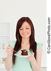Attractive red-haired woman eating some cake in the kitchen