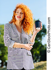 Attractive red haired woman going to drink coffee