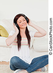 Attractive red-haired woman listening to music with headphones while sitting on a carpet in the living room