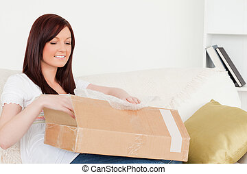 Attractive red-haired woman opening a carboard box while sitting on a sofa in the living room