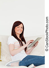 Attractive red-haired woman relaxing with her tablet while sitting on a sofa in the living room