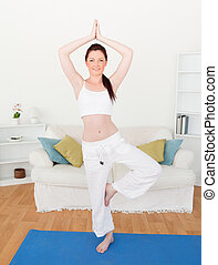 Attractive red-haired woman stretching in the living room in...