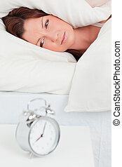 Attractive red-haired woman waking up thanks to an alarm clock