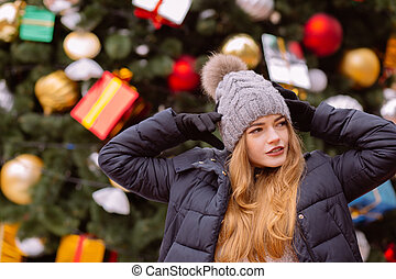 Attractive red haired woman wearing winter outfit, posing on the background of Christmas spruce