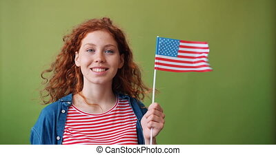 Attractive redhead teenager holding American flag on green...