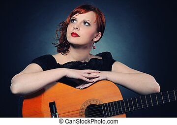 Attractive redhead woman with guitar