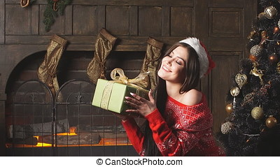 Attractive redheaded girl holding Christmas gift and smiling.