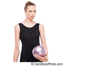 attractive rhythmic gymnast in leotard smiling and holding ball isolated on white